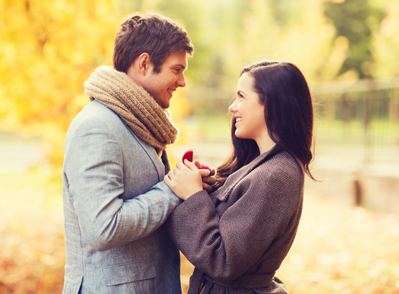 marry me: love, relationship, family and people concept - close up of smiling couple with red gift box in autumn park