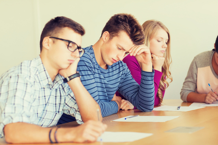 difficult task: education, school, test and people concept - group of students with papers thinking or making test