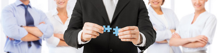 business, development, team building and people concept - close up of man trying to connect puzzle pieces over group of partners background
