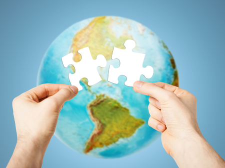 globe puzzle: ecology, energy saving, people and environment concept - close up of male hands trying to connect white puzzle pieces over earth globe on blue background