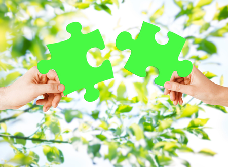 natural energy: nature, ecology, energy saving, people and environment concept - close up of couple hands trying to connect green puzzle pieces over natural background Stock Photo