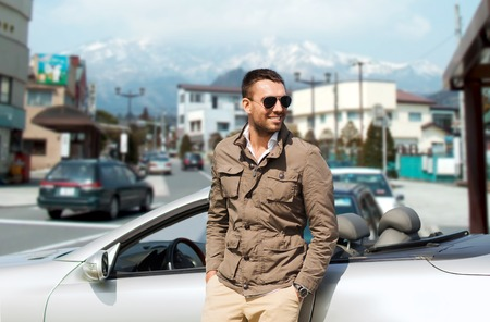 asia style: travel, tourism, transport, leisure and people concept - happy man near cabriolet car over city in japan background