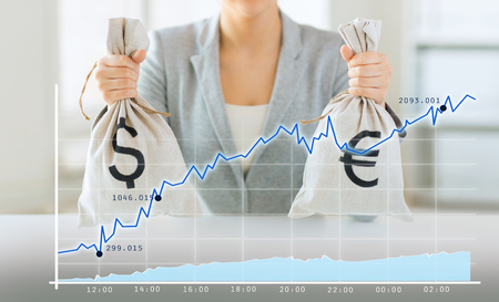 charts graphs: business, finance, saving, banking and people concept - close up of woman hands holding dollar and euro money bags with growing chart Stock Photo