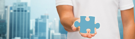 urbanization: business, development, urbanization and people concept - close-up of man holding blue puzzle piece over city background