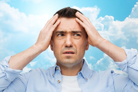 sad face: stress, headache, health care and people concept - unhappy man with closed eyes touching his forehead over blue sky and clouds background