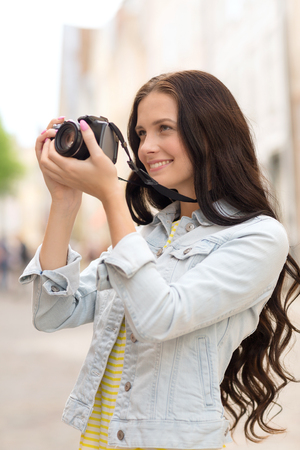 camera girl: tourism, travel, leisure, holidays and friendship concept - smiling teenage girl with camera taking picture on street