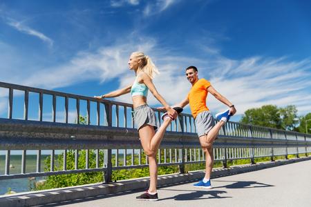 fitness, deporte, entrenamiento y estilo de vida concepto - sonriente pareja extiende al aire libre