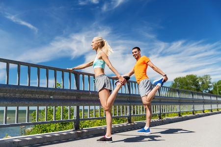 fitness, sport, training and lifestyle concept - smiling couple stretching outdoors Stock Photo - 57581042