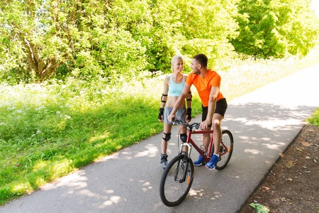 rollerblades: fitness, sport, summer, people and healthy lifestyle concept - happy couple with rollerblades and bicycle riding and talking outdoors at summer Stock Photo