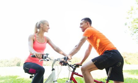 pareja saludable: fitness, sport, people and healthy lifestyle concept - happy couple riding bicycle outdoors at summer