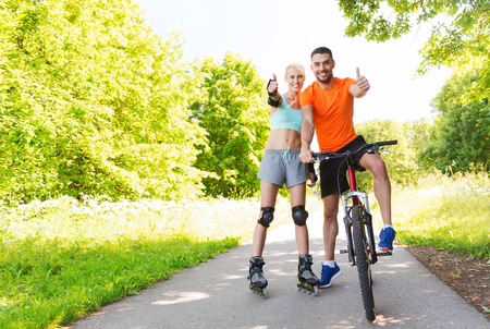 rollerblades: fitness, sport, summer, people and healthy lifestyle concept - happy couple with rollerblades and bicycle showing thumbs up outdoors at summer
