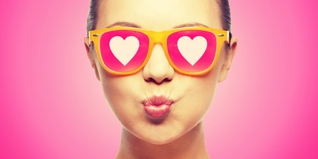 love, happiness, valentines day, face expressions and people concept - portrait of teenage girl in pink sunglasses with hearts blowing kiss