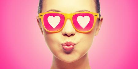 Liebe, Glück, valentinstag, Gesichtsausdrücke und Personen Konzept - Porträt von Teenager-Mädchen in rosa Sonnenbrille mit Herz weht Kuss
