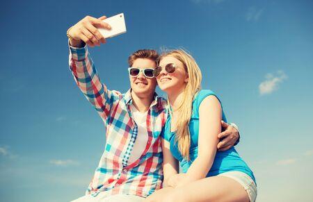 pareja de adolescentes: días de fiesta, vacaciones, el amor y la amistad concepto - sonriente pareja que se divierten al aire libre Foto de archivo