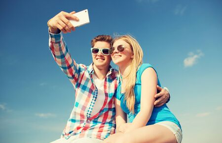 teenage couple: holidays, vacation, love and friendship concept - smiling couple having fun outdoors Stock Photo