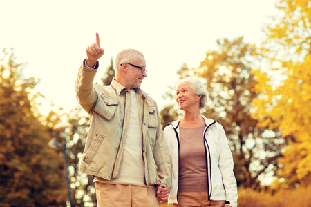retired couple: family, age, tourism, travel and people concept - senior couple pointing finger and walking in park Stock Photo