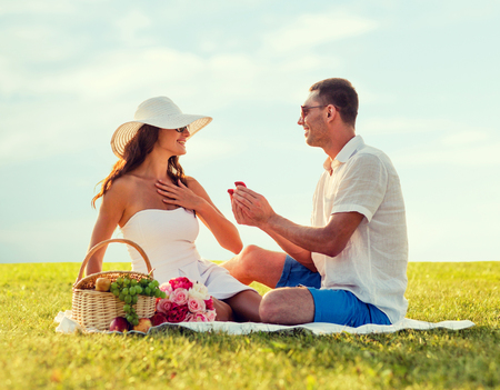 engagements: love, dating, people, proposal and holidays concept - smiling young man giving small red gift box with wedding ring to his girlfriend on picnic over blue sky and grass background Stock Photo