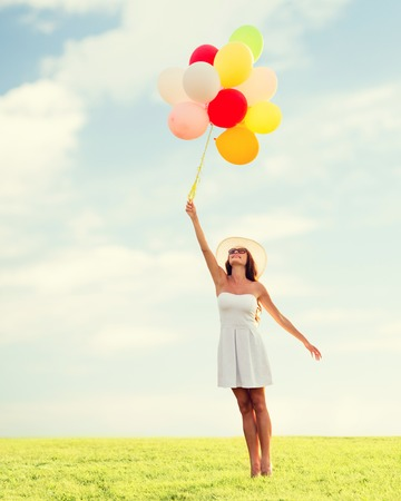 bird flying: happiness, summer, holidays and people concept - smiling young woman wearing sunglasses with balloons over blue sky and grass background