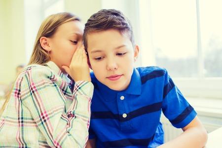 educación, escuela primaria, el aprendizaje y el concepto de la gente - sonriendo colegiala susurrando secreto a oreja compañero de clase en el aula