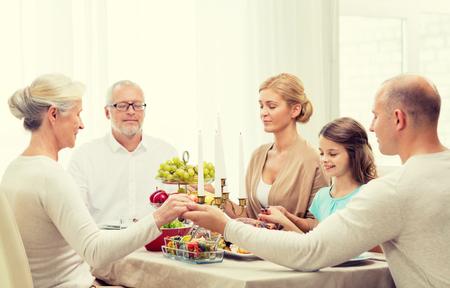 familia, días de fiesta, la generación y el concepto de la gente - familia sonriente de la cena y la oración en el hogar Foto de archivo