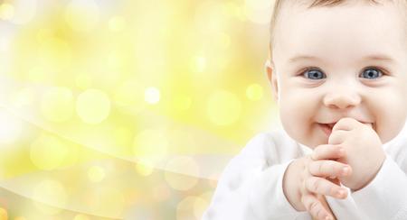 bebes recien nacidos: personas, niños y Vida de bebé - cerca de la del bebé feliz sobre fondo amarillo Foto de archivo