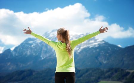 mujeres de espalda: Fitness, deporte, peope y emociones concepto - feliz mujer en ropa deportiva disfrutando del sol y la libertad sobre las montañas y el cielo azul de fondo de la espalda