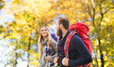Abenteuer, Reisen, Tourismus, Wanderung und Menschen Konzept - lächelnde Paar mit Rucksäcken über natürlichen Hintergrund zu Fuß