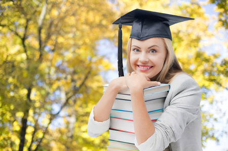 book concept: education, school, knowledge, graduation and people concept - happy smiling student girl in bachelor cap with books over autumn trees background