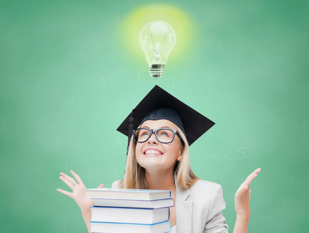 trencher: education, school, knowledge, graduation and people concept - happy student girl in bachelor cap with books over green chalk board background Stock Photo