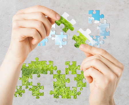 puzzle background: nature, ecology saving, people and environment concept - close up of hands trying to connect puzzle pieces with blue sky and grass over cracked concrete or asphalt background