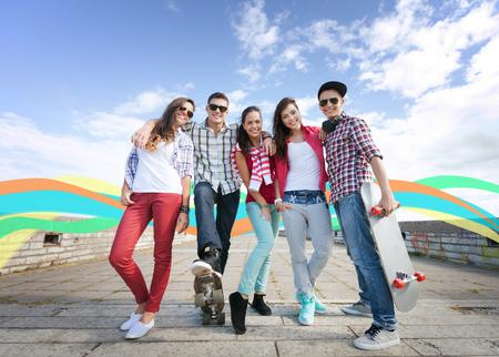 vacaciones de verano y el concepto de adolescentes - grupo de adolescentes con los patines fuera Foto de archivo