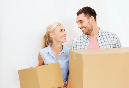 'young things': home, people, repair and real estate concept - happy couple holding cardboard boxes and moving to new place Stock Photo