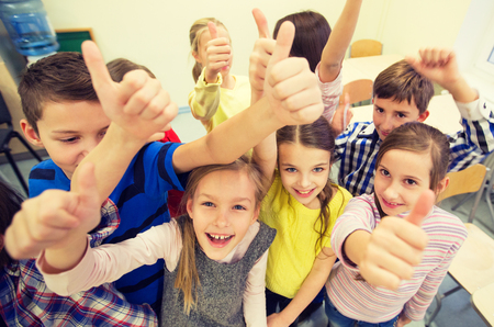 'teenager boy: education, elementary school, learning, gesture and people concept - group of school kids and showing thumbs up in classroom