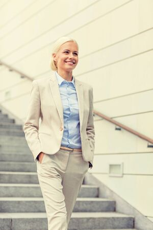 down the stairs: negocio, la gente y el concepto de la educación - joven empresaria sonriente caminando por las escaleras al aire libre Foto de archivo
