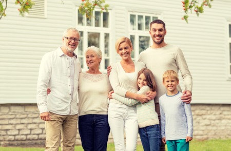 three generations: family, happiness, generation, home and people concept - happy family standing in front of house outdoors Stock Photo