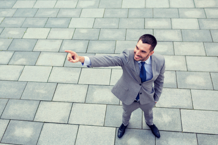 people development: business, development and people and concept - young smiling businessman pointing finger outdoors from top