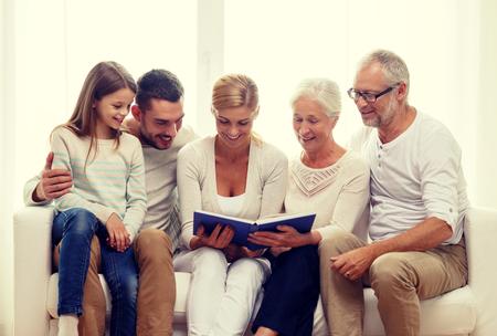 concept de famille, bonheur, génération et personnes - famille heureuse avec livre ou album photo assis sur le canapé à la maison