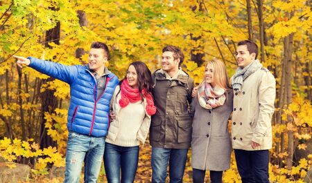 dedo señalando: love, relationship, season, friendship and people concept - group of smiling men and women hugging in autumn park Foto de archivo
