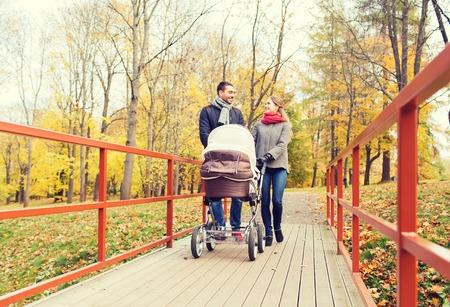 l'amour, la paternité, la famille, la saison et les gens notion - souriant couple avec bébé poussette dans le parc de l'automne