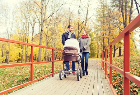 family walking: love, parenthood, family, season and people concept - smiling couple with baby pram in autumn park
