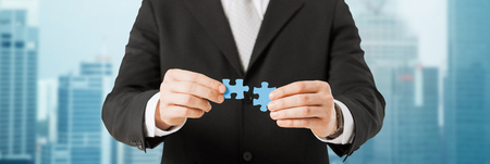 affaires, le développement et les gens concept - close up de l'homme tente de se connecter des pièces de puzzle sur la ville de fond