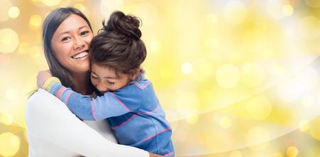 mensen, moederschap, familie, vakantie en adoptie concept - gelukkige moeder en dochter knuffelen op gele achtergrond verlichting