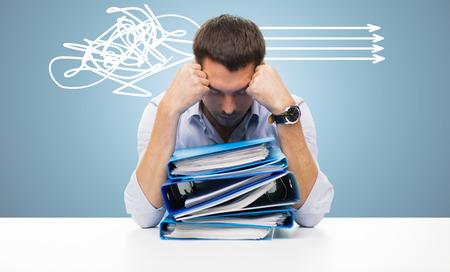 negocio, la gente, plazo, el estrés y el concepto de papeleo - hombre de negocios triste con la pila de carpetas sobre fondo azul y las flechas Foto de archivo
