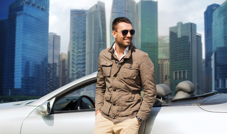 city road: travel, tourism, road trip, transport and people concept - happy man near cabriolet car over city skyscrapers background