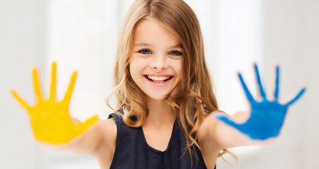 painted: education, school, art and happiness concept - little student girl showing hands in yellow and blue color at school
