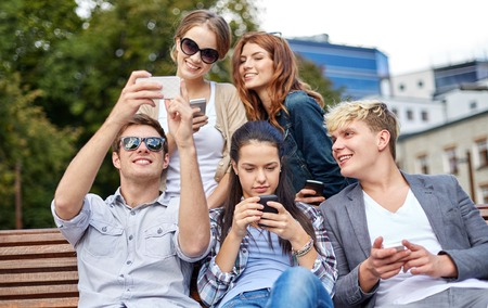 mobile internet: summer, technology, education and teenage concept - group of happy students or teenagers with smarphones taking selfie and texting messages at campus