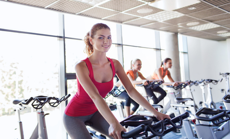 gym workout: sport, fitness, lifestyle, equipment and people concept - group of women riding on exercise bike in gym