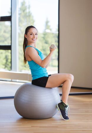 fitness gym: fitness, sport, training and people concept - smiling woman with dumbbells and exercise ball flexing muscles in gym