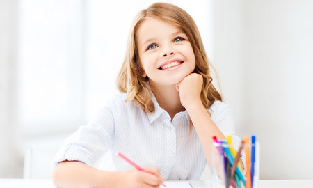 daydreaming: smiling little student girl drawing and daydreaming at school