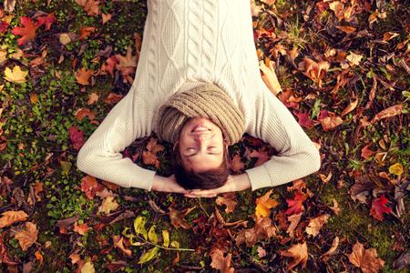 alegria: temporada, la felicidad y el concepto de la gente - sonriente joven tendido en el suelo o la hierba y las hojas caídas en el parque del otoño